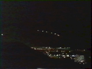 Phoenix Lights photo - geometrical formation of 6 objects to right with 1 brighter object to left, above city lights
